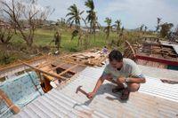 En man lappar ihop sitt hus efter den förödande cyklonen Winston, som drabbade Fiji 2016.