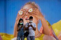Ett par med ansiktsmask framför en stor affisch i Hongkong. Hårda restriktioner har införts efter ett ökat antal smittfall i landet.