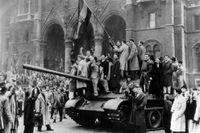 Invånare från Budapest reser den ungerska flaggan på en erövrad rysk pansarvagn.