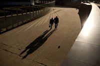 Ett äldre par njuter av höstsolen vid EU-kommissionens Berlaymont-byggnad i Bryssel. Arkivfoto.
