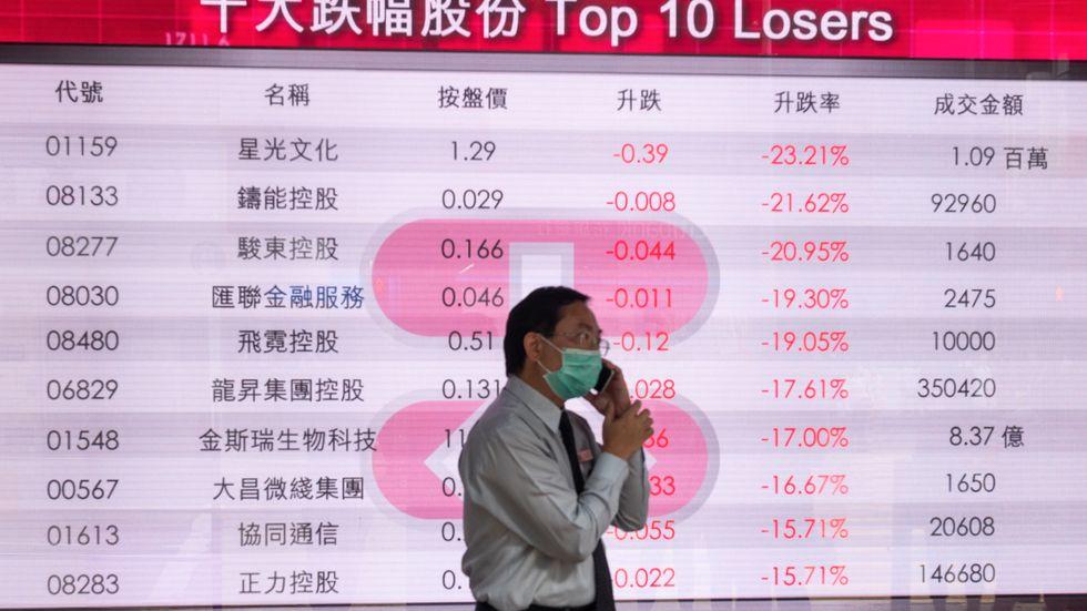 En man med ansiktsmask talar i mobiltelefon framför kurserna på Hongkongbörsen. Virus och finansiella rusningar kan spridas på ett likartat sätt.