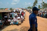 Rohingyaflyktingar håller upp lappar med sina budskap när FN:s säkerhetsråds delegation besöker det enorma flyktinglägret i Bangladesh.