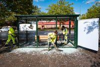 Personal från Malmö stad röjer upp krossat glas från en krossad busskur i Rosengård i Malmö.