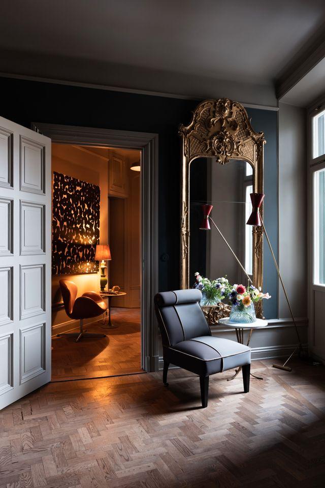 Arne Jacobsens fåtölj Svanen, som följt med familjen från hem till hem, står i den inre hallen. Framför spegeln på ett sidobord i stora hallen står Carina Seth Anderssons vas  Stubbe.