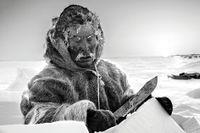 """Simon Qamanirg bygger en igloo i Nunavut, Kanada. Ur fotoboken """"Encounter""""."""
