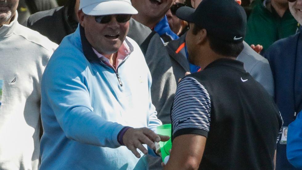 En åskådare ger tillbaka golfbollen till Jason Day efter att australierns utslag på Augusta Nationals första hål under US Masters landat i mannens ölglas.