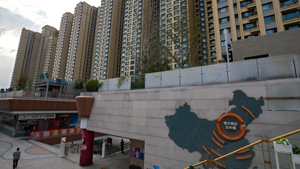 En karta över krisdrabbade Evergrandes fastighetsutvecklingsprojekt syns på en husfasad i ett köpcentrum i Peking med ett av koncernens bostadskomplex i bakgrunden.