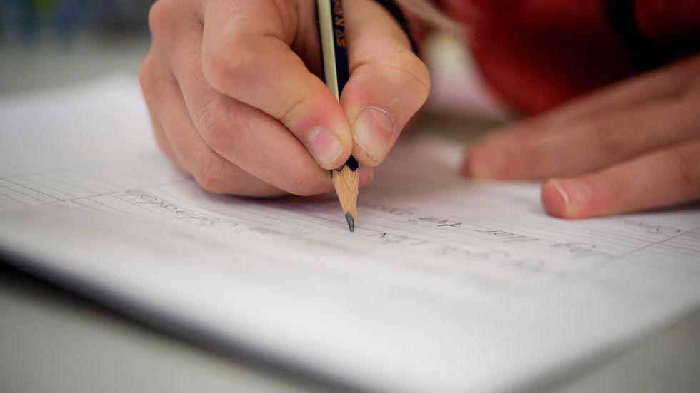 En elev skriver för hand med en blyertspenna. Arkivbild