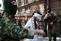 Maskerade pro-ryska män och den ukrainska journalisten Irma Krat i östra Ukraina i april.