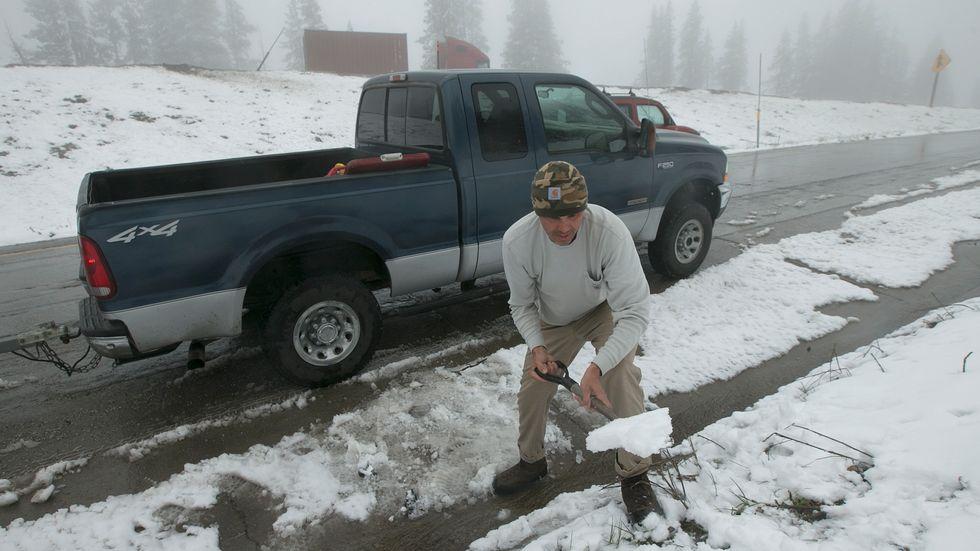 Kaliforniern George Harrison samlar nyfallen snö för att kyla ner fisk han fångat i Donner Lake, Kalifornien, i måndags.
