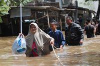 Boende vadar fram och får hjälp att hålla balansen med ett uppsatt rep i Tanggerang utanför Jakarta.