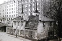 I huset på bilden (tagen 1925) bodde 31 personer på övervåningen på 1870-talet. Byggnaden stod där trafiken i dag susar fram på Sveavägen i korsningen med Frejgatan.
