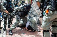 Kravallpolis ingriper mot en demonstrant i Hongkong den 1 juli.