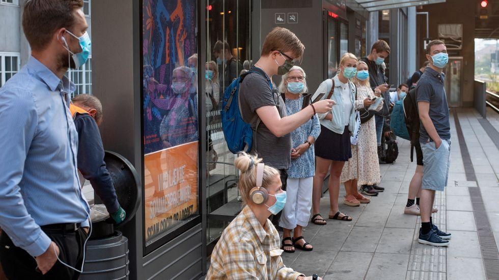 Passagerare med munskydd väntar på tåget i Århus i Danmark.