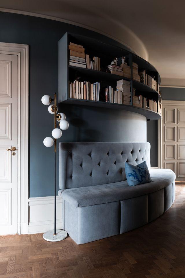 Hallen är stor och rymlig, förvaringen har man löst med  utdragbara lådor under soffan. Bokhyllan är platsbyggd för att forma sig efter den rundade väggen. Golvlampan kommer från Dusty deco.