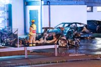 Polis och räddningstjänst på plats vid vraken efter de utbrända elbilarna utanför Teslas sevicecenter i Malmö tidigt på tisdagsmorgonen.