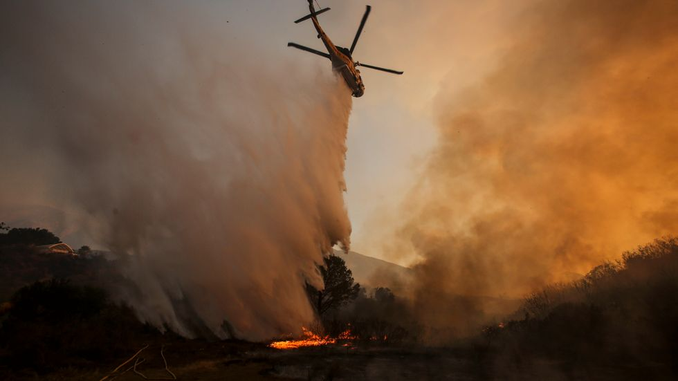 A helicopter makes a drop on a wildfire near Placerita Canyon Road in Santa Clarita, Calif. The smoky fire tore through drought-ravaged brush that hadn't burned in decades amid a sweltering heat wave and exploded over the weekend.