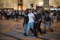 En person förs bort av polis i samband med demonstrationerna i Hongkong på tisdagskvällen.