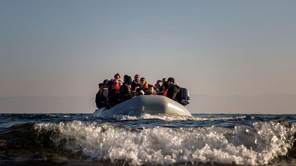 """I den engelska bildtexten till bilden från den 7 december står det att """"refugees and migrants"""" anländer till den grekiska ön Lesbos. Artikelförfattaren kritiserar att svenska politiker och medier inte håller isär människor som flyr och människor som vill bosätta sig någon annanstans."""