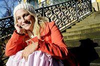 """Ann Söderlund i färgglada kläder på trappan till Katarina kyrka. Ann känner att hon hör hemma på Södermalm, """"inte minst klädmässigt""""."""