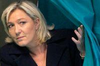 Marine Le Pen går ut ur ett röstningbås under franska lokalvalen i mars i år.
