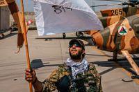 En taliban viftar med en flagga på flygplatsen i Kabul
