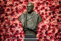 Bysten av Alfred Nobel framför en vägg av blommor i Konserthuset.
