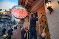 Personal på en pizzeria i New Orleans stormsäkrar lokalen inför orkanen Idas ankomst.