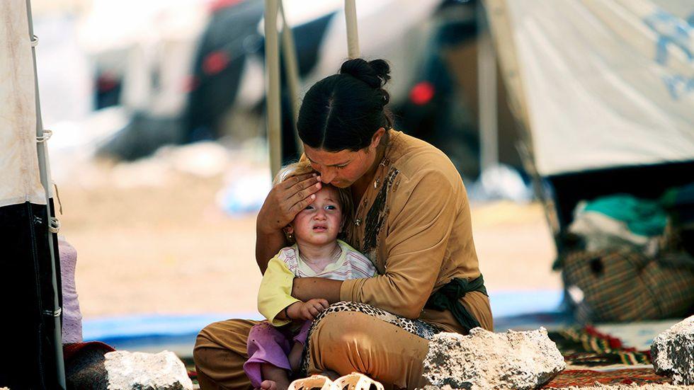 En yazidisk kvinna, som flytt från den irakiska staden Sinjar, sitter med sin dotter i ett tält i flyktinglägret Nowruz i nordöstra Syrien.
