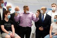 Israels premiärminister Naftali Bennett, till höger i mörk kostym, lyssnar på hälsominister Nitzan Horowitz i lila skjorta under ett besök på ett sjukhus i juni.