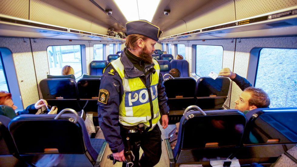 Polis kontrollerar id-kort och pass för resande på tåget från Danmark.