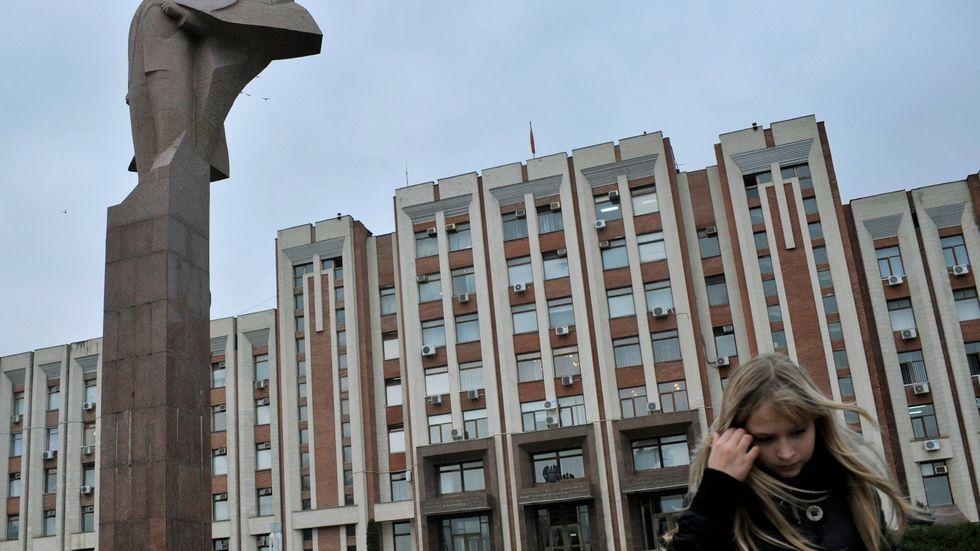En flicka går förbi en Leninstaty framför parlamentet i Transnistriens huvudstad Tiraspol. Moldaviska parlamentsledamöter kräver att Ryssland drar tillbaka sina styrkor från utbrytarregionen. Arkivbild.