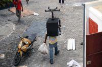 En man i Port-au-Prince bär iväg på en stol under plundringarna av butiker i staden.