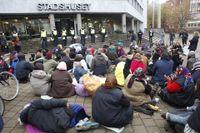 EU-migranter demonstrerar utanför stadshuset efter utrymyningen av lägret.