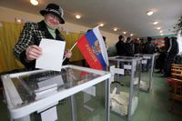 En kvinna lägger sin röst vid folkomröstningen på Krim i mars.