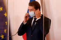 Österrikes förbundskansler Sebastian Kurz rättar till sitt munskydd vid en presskonferens i Wien.