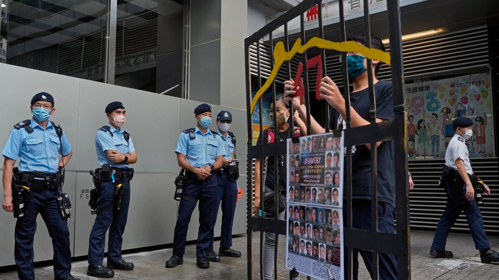 Polis i Hongkong bevakar en demonstration mot valsystemet under söndagen.