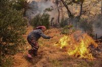 En kvinna försöker hindra eldens framfart nära Antalya.