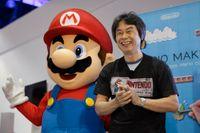 Shigeru Miyamoto bredvid tv-spelsikonen Mario, en  av hans mest kända skapelser.
