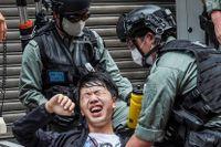 En reporter faller till marken efter att ha sprejats med pepparsprej av polisen.