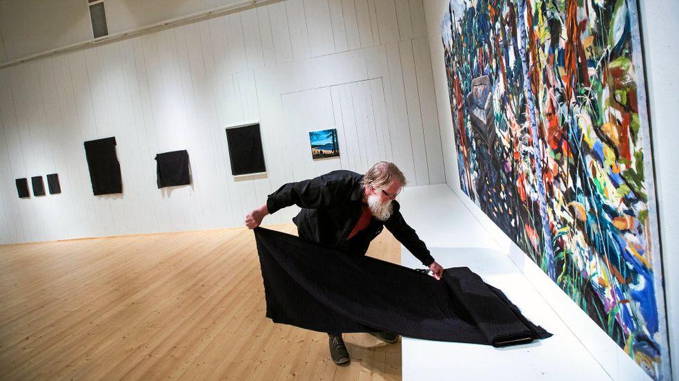 Mikael Arvidsson täcker över sina verk vid en protest på Länsmuseet i Härnösand.