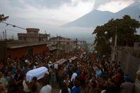 Invånare i byn San Juan Alotenango bär de döda till kyrkogården efter att Volcán de Fuego, som syns i bakgrunden, fått sitt utbrott.