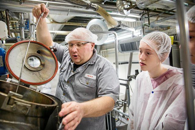 Piotr, produktionsledare, visar juniorreportrarna hur det går till när godis tillverkas.