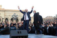 Armeniens president Nikol Pasjinian hälsar anhängare vid ett tal sedan han anklagat militär för att planera en kupp.