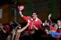 """""""Chavez lever"""" står det på skylten som Venezuelas president Nicolas Maduro håller upp."""