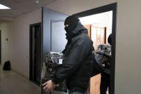 Polisen bär iväg beslagtagna dokument och datorer från människorättsorganisationen Vjasnas kontor i Minsk i Belarus.
