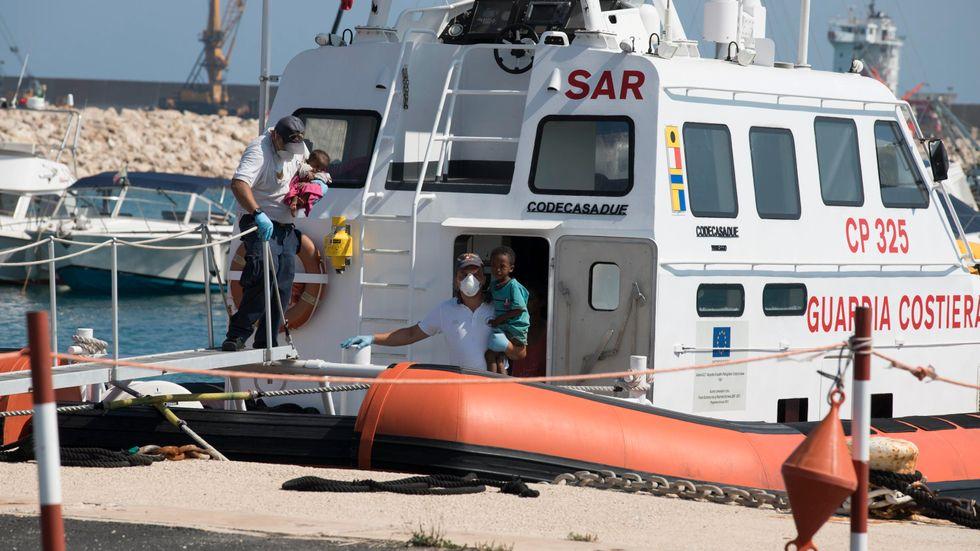 Barn släpps i land av ett italiensk fartyg vid hamnen Pozzallo i södra Italien under söndagen.