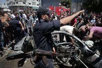Palestinier söker igenom ett bilvrak efter det att israeliskt flygvapen slagit till mot Gaza City.