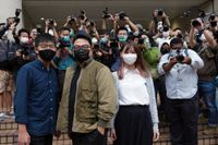 Joshua Wong (till vänster) framför domstolsbyggnaden tillsammans med aktivisterna Ivan Lam och Agnes Chow, som också står inför rätta.