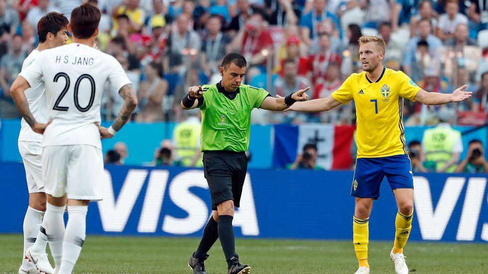 Sebastian Larsson (i gult) skriker på domare Joel Aguilar att blåsa straff. Det gjorde Aguilar, efter videogranskning.